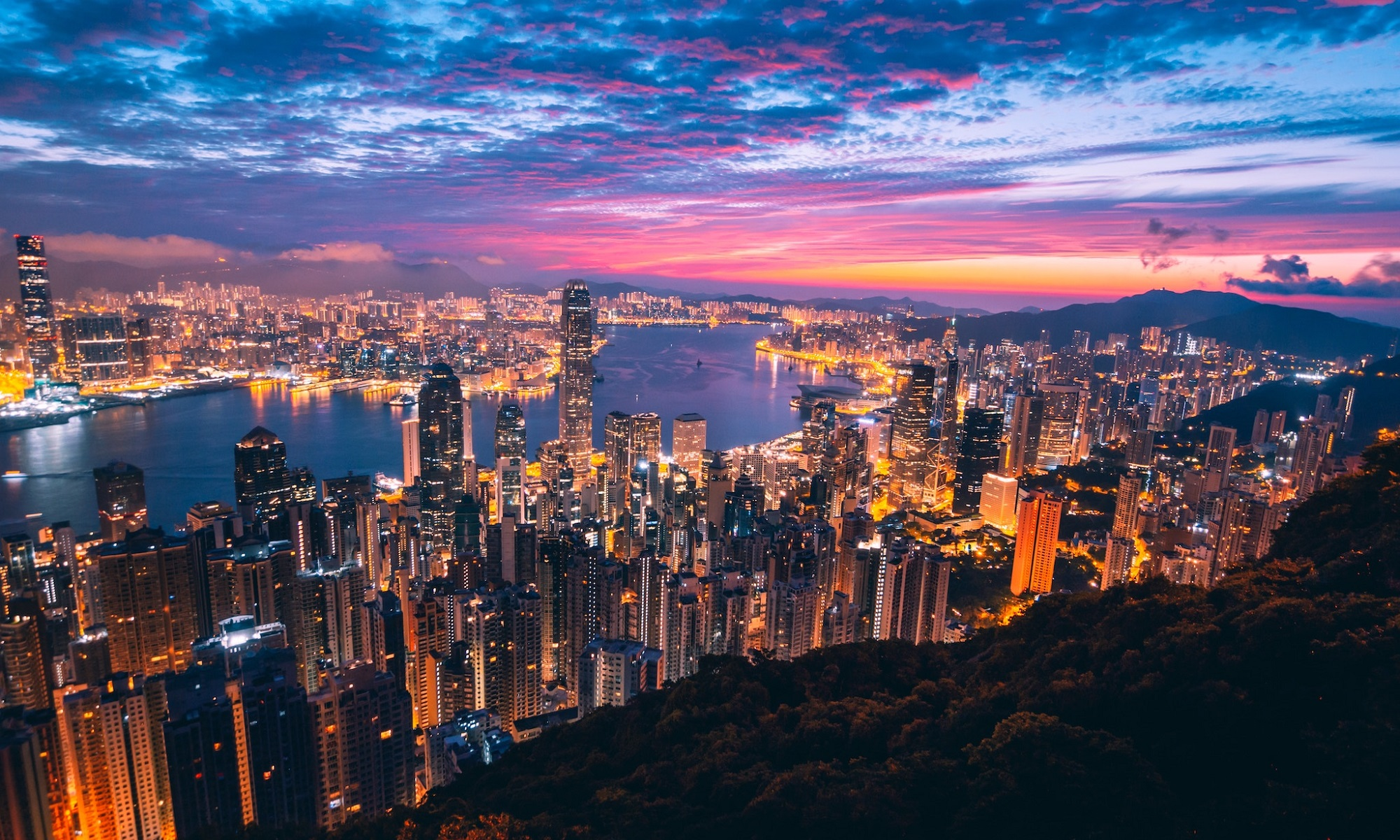 Panorama view of Hong Kong bay from Victoria Peak summit at sunset.